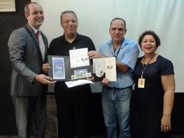 O diretor regional dos Correios no Espírito Santo, Rafael Carpanedo Fiorio, entrega o álbum especial em couro ao filatelista Marcos Boaventura. Ao lado, Jairo Mansur e Neusa Wetler